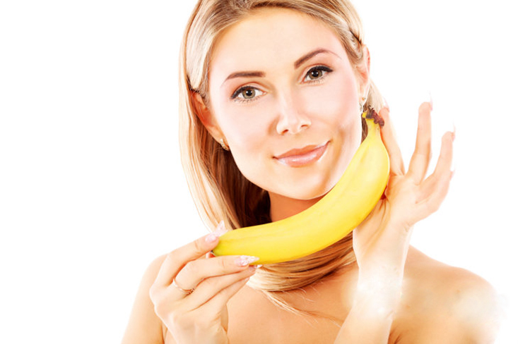Portrait of a beautiful young woman holding bananas.